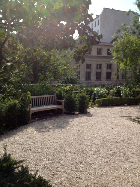 An empty park bench at lunch time in a lovely public garden. Only in August.
